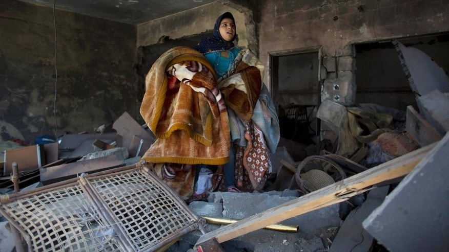 A Palestinian girl salvages blankets from a destroyed house in the heavily bombed Gaza City neighborhood of Shijaiyah, close to the Israeli border, Friday, Aug. 1, 2014. (AP Photo/Dusan Vranic)