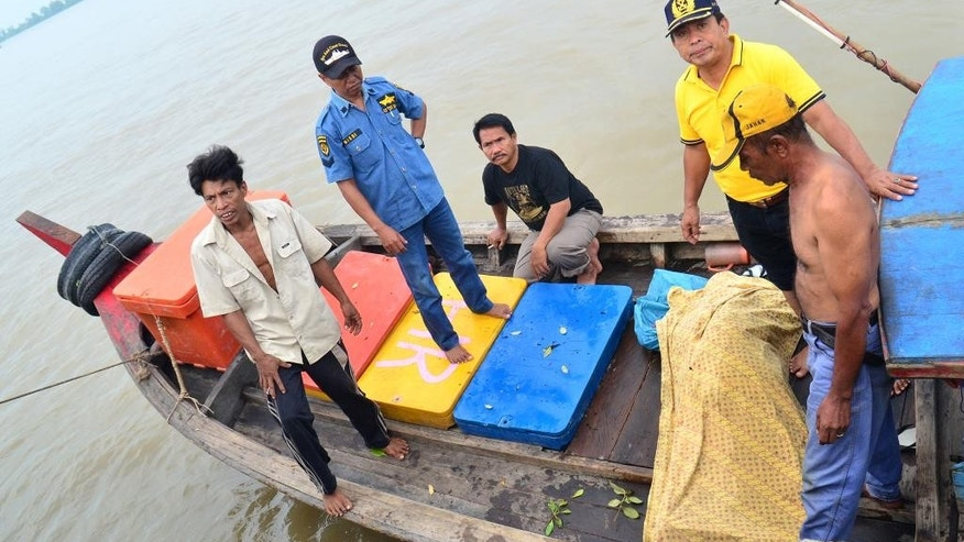 Rescuers carry  the body of one of the victims of a boat accident in North Sumatra, Indonesia, Friday, Aug. 1, 2014. A boat carrying villagers to their hometown to celebrate the end of Ramadan sank Thursday after hitting a stump in a river, an official said. (AP Photo)