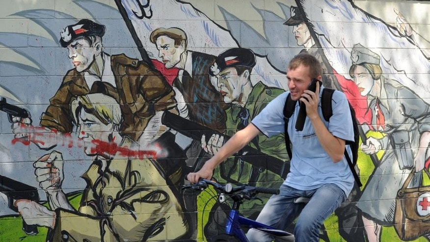 A cyclist rides past a mural dedicated to the Warsaw Uprising 1944 insurgents in Warsaw, Poland, Thursday, July 31, 2014, on the eve of state ceremonies marking 70 years since the thousands of young Warsaw residents put up a fight against the occupying Nazis. The poorly armed insurgents, mostly with little military training, held on for 63 days in the cut-off city, inflicting heavy losses on the well-armed and trained German troops before being forced to surrender. (AP Photo/Alik Keplicz)