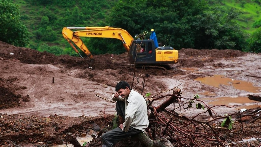 Chandrakant Zanjare, who said he lost 13 family members to a landslide, wails near the site where his house stood in Malin village, in the western Indian state of Maharashtra, Friday, Aug. 1, 2014. Heavy rains hampered efforts Friday by hundreds of rescue workers digging through heavy mud and debris, as the death toll from a landslide that engulfed an entire village in western India crossed 50. (AP Photo/Rafiq Maqbool)
