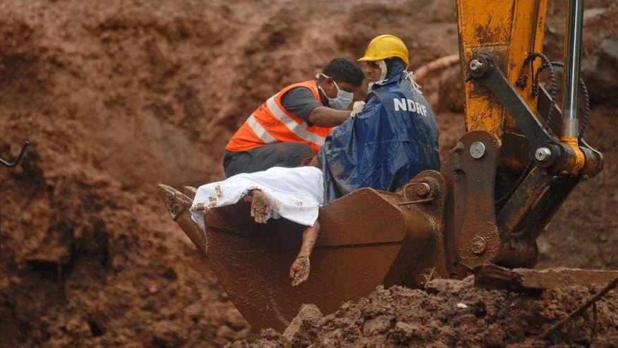 In this Thursday, July 31, 2014 photo, the limp hands of a victim hang as rescuers recover the body from the site of a landslide in Malin village, in the western Indian state of Maharashtra. Heavy rains hampered efforts Friday by hundreds of rescue workers digging through heavy mud and debris, as the death toll from a landslide that engulfed an entire village in western India crossed 50. (AP Photo/Nitin Lawate)