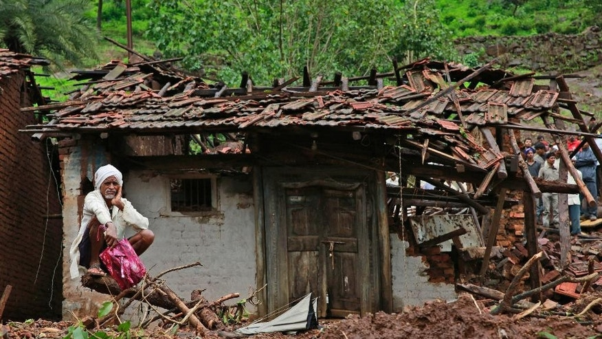 A villager watches a rescue operation sitting by his damaged house at the site of a landslide in Malin village, in the western Indian state of Maharashtra, Friday, Aug. 1, 2014. Heavy rains hampered efforts Friday by hundreds of rescue workers digging through heavy mud and debris, as the death toll from a landslide that engulfed an entire village in western India crossed 50. (AP Photo/Rafiq Maqbool)