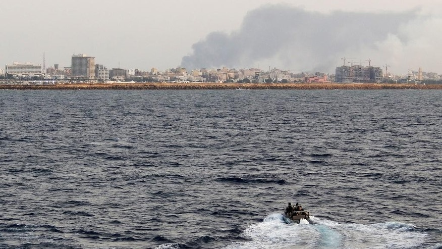 In this handout photo provided by the Hellenic Navy, a navy special operations team inspects waters as a plume of smoke is seen over Libya's capital Tripoli on Thursday, July  31, 2014. A Greek frigate was was used to evacuate Greek embassy staff and others from Tripoli. The navy said 186 people, including the Embassy staff, other Greek nationals and citizens from China, Britain, Belgium, Russia and Albania were being transported to a port near Athens. With the violence in Libya escalating to its worst level since the 2011 ouster of dictator Moammar Gadhafi, governments from around the world are scrambling to evacuate their citizens from the country, many seeking help from nearby Greece.(AP Photo/Hellenic Navy)