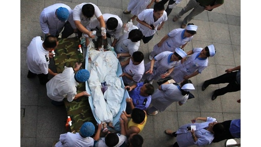 August 2, 2014: Medical staff move a severely burnt victim of an explosion at an eastern Chinese automotive parts factory from a hospital in the city of Kunshan, Jiangsu province  to a Shanghai hospital which is better equipped to handle severe burns. Dozens of people were killed Saturday by the explosion at the factory that supplies General Motors, state media reported. (AP Photo)
