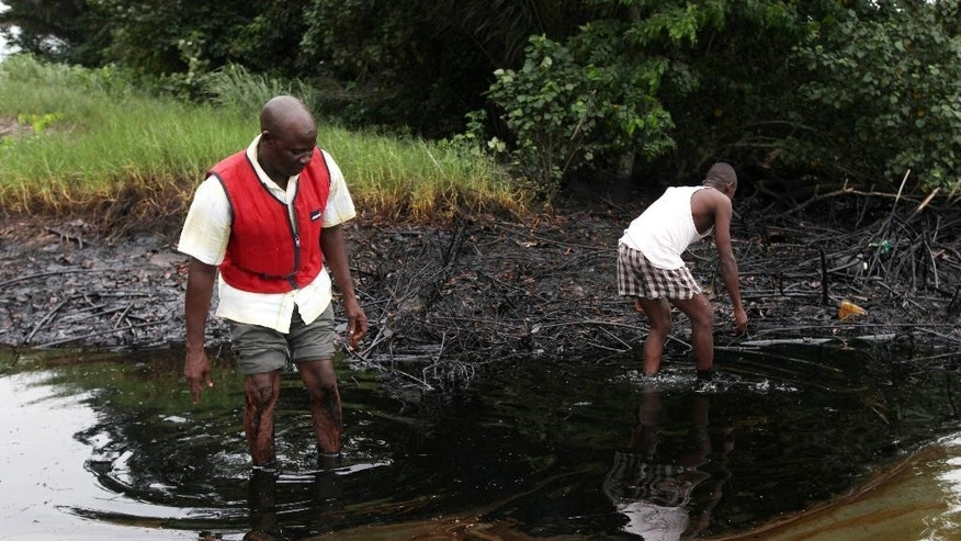 FILE - In this June 20, 2010 file photo, men walk in an oil slick covering a creek near Bodo City in the oil-rich Niger Delta region of Nigeria. Little action has been taken to clean up pollution caused by oil production in Nigeria's Niger Delta region, either by the government or Shell Oil, Amnesty International and other groups charged Monday. Aug. 4, 2014. Oil production has contaminated the drinking water of at least 10 communities in the Ogoniland area but neither the Nigerian government nor Royal Dutch Shell's Nigeria subsidiary have taken effective measures to restore the fouled environment, said the new report by Amnesty International, Friends of The Earth Europe, Center for Environment, Human Rights and Development, Environmental Rights Action, and Platform.  (AP Photo/Sunday Alamba, File)