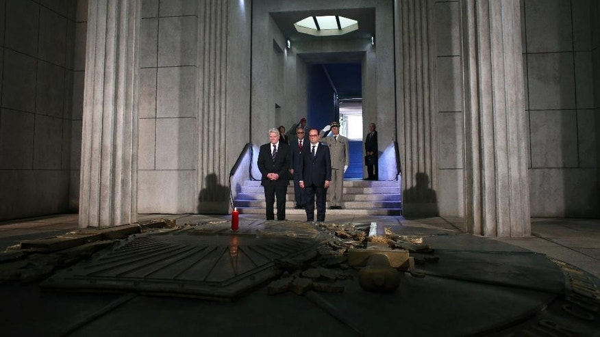 France's President Francois Hollande, right, stands next to German President Joachim Gauck, left, as they pay respect in the crypt of the the National Monument of Hartmannswillerkop, in Wattwiller, eastern France, Sunday, August 3, 2014, to mark the 100th anniversary of the outbreak of World War I. On this day 100-years ago, in 1914, Germany declared war on France, at the beginning of the first global war, which centred on Europe and resulted in over nine million combatants being killed. (AP Photo/Thibault Camus, Pool)