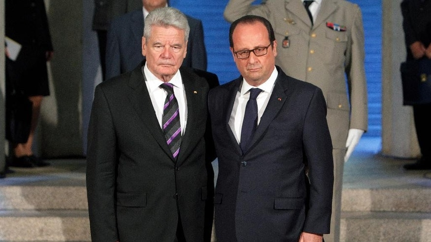 France's President Francois Hollande, right, stands next to German President Joachim Gauck, left, as they pay respect in the crypt of the the National Monument of Hartmannswillerkop, in Wattwiller, eastern France, Sunday, August 3, 2014, to mark the 100th anniversary of the outbreak of World War I. On this day 100-years ago, in 1914, Germany declared war on France, at the beginning of the first global war, which centred on Europe and resulted in over nine million combatants being killed.(AP Photo/Thibault Camus, Pool)