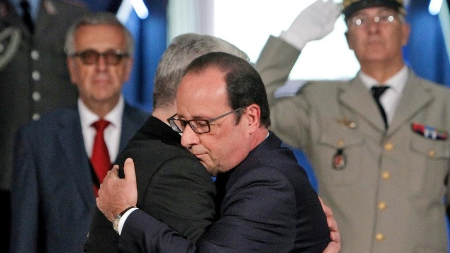 France's President Francois Hollande, right, hugs German President Joachim Gauck, left, as they pay respect in the crypt of the the National Monument of Hartmannswillerkop, in Wattwiller, eastern France, Sunday, August 3, 2014, to mark the 100th anniversary of the outbreak of World War I. On this day 100-years ago, in 1914, Germany declared war on France, at the beginning of the first global war, which centred on Europe and resulted in over nine million combatants being killed.(AP Photo/Thibault Camus, Pool)