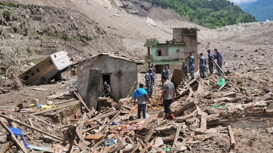 August 2, 2014: Nepalese security personnel gather for rescue work at the site of a landslide in Sindhupalchowk area, about 75 miles east of Katmandu. A massive landslide killed at least eight people and blocked a mountain river in northern Nepal on Saturday, causing the water to form a lake that was threatening to burst and sweep several villages, officials said. (AP Photo/Dinesh Gole)