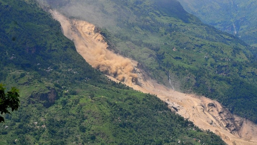 A cloud of dust rises as loose earth moves down a slope at the site of a landslide in Sindhupalchowk area, about 120 kilometers (75 miles) east of Katmandu, Nepal, Saturday, Aug. 2, 2014. A massive landslide killed at least eight people and blocked a mountain river in northern Nepal on Saturday, causing the water to form a lake that was threatening to burst and sweep several villages, officials said. (AP Photo/Dinesh Gole)