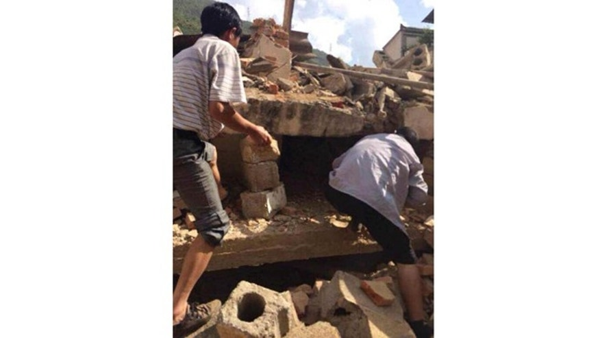 Aug. 3, 2014: In this photo taken by cellphone and released by China's Xinhua News Agency, men at rubbles of buildings look for survivors after an earthquake in Ludian County of Zhaotong City in southwest China's Yunnan Province. (AP)