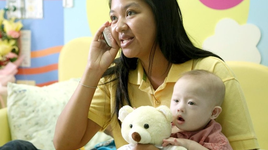 Pattaramon Chanbua, 21, talks on a mobile phone while holding her son Gammy at a hospital in Chonburi province, southeastern Thailand Sunday, Aug. 3, 2014. The Australian government is consulting Thai authorities after news emerged that Gammy, a baby with Downs Syndrome was abandoned with Chanbua, his surrogate mother, in Thailand by his Australian parents, according to local media. (AP Photo/Apichart Weerawong)