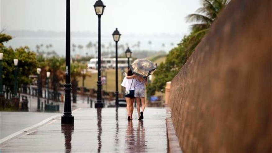 Two women walk with the protection of an umbrella in Old San Juan, Puerto Rico, Saturday, Aug. 2, 2014. Bertha pushed just south of Puerto Rico on Saturday as it unleashed heavy rains and strong winds across the region. (AP Photo/Ricardo Arduengo)
