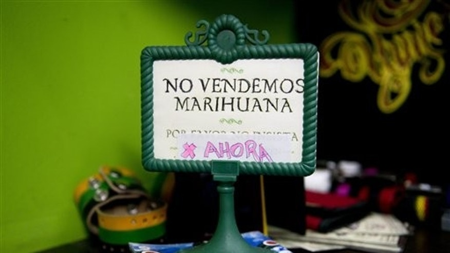 "FILE - This May 6, 2014 file photo shows a sign that reads in Spanish; ""We don't sell pot, yet,"" on display at a head shop in downtown Montevideo, Uruguay. Delays in implementing the plan to create the worlds first national, government-regulated marketplace for legal pot , are putting it at risk as polls point to opposition gains in October general elections and disapproval of the project by most Uruguayans. (AP Photo/Matilde Campodonico, File)"