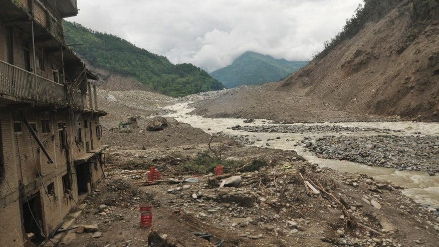 The scene after a massive landslide in village Mankha, about 120 kilometers (75 miles) east of Katmandu, Nepal, Sunday, Aug.3, 2014. Nepalese officials say there is no chance of finding any of the more than 150 people, who are believed to have been buried by the early Saturday landslide in northern Nepal. (AP Photo/Arpan Shrestha)
