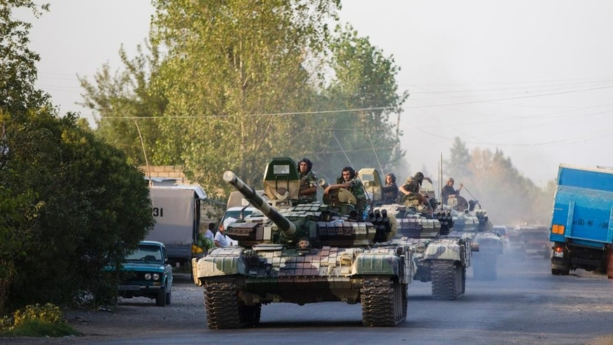 In this Saturday, Aug. 2, 2014, photo a convoy of Azerbaijan's Army tanks moves in the direction of Agdam, Azerbaijan.  Recent days have seen a sharp escalation in fighting between Azerbaijan and Armenia around a tense line of control around Nagorno-Karabakh. (AP Photo/Abbas Atilay )