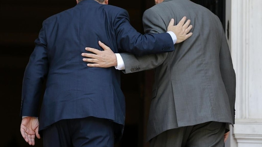 Jean-Claude Juncker, president-elect of the European Commission, left, and Greece's Prime Minister Antonis Samaras enter the Maximos Mansion in Athens, Monday, Aug. 4, 2014. Juncker is visit Athens in his first trip since his election by the new European Parliament last month. He meets Samaras, a fellow conservative, to express support for the country's ongoing effort to make its public finances sustainable. (AP Photo/Thanassis Stavrakis)