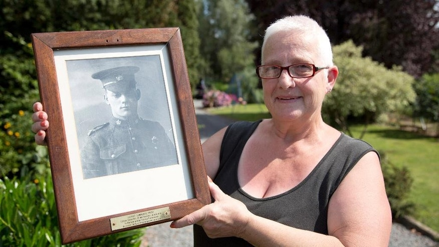 Resident Marilyn Lahaeu holds up a photo of World War I soldier Pvt. George Lawrence Price, who was killed in the Belgian village of Ville-sur-Haine, in 1918, near her home in Ville-sur-Haine, Belgium, Sunday, Aug. 3, 2014. An international ceremony will take place on Monday, Aug. 4, 2014 at St. Symphorien Cemetery near Mons, Belgium to commemorate 100 years since the start of WWI. Pvt. George Lawrence Price was killed in action on Nov. 11, 1918 just two minutes before the Armistice. He is known as the last Canadian soldier to die on the Western Front in the First World War. (AP Photo/Virginia Mayo)