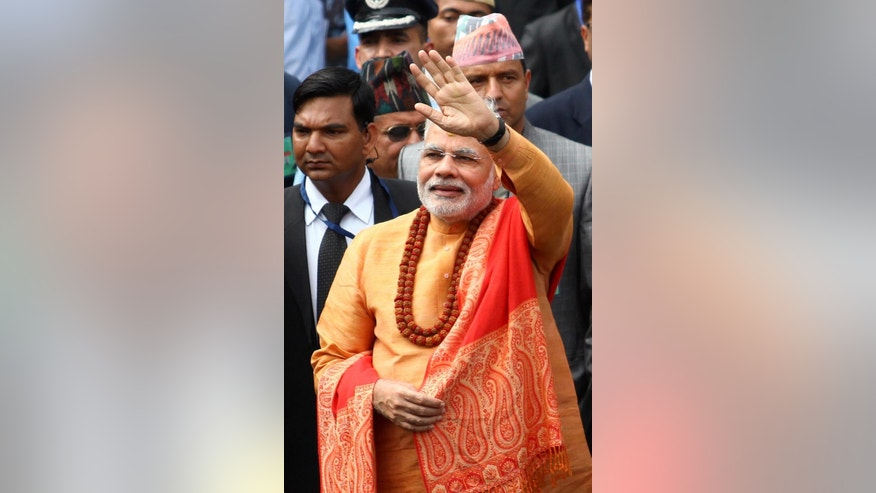 Indian Prime Minister Narendra Modi, waves to the crowd as he leaves after offering prayers at the Pashupatinath Hindu Temple in Katmandu, Nepal, Monday, Aug. 4, 2014. Modi arrived in Nepal on Sunday to meet with top leaders, offer prayers at this revered Hindu temple and address parliament. (AP Photo/Kiran Panday)