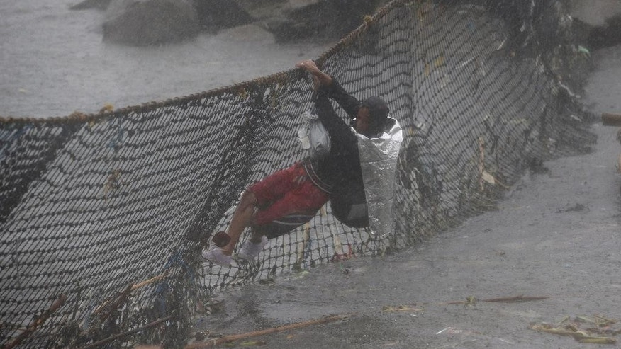 A Filipino man hangs on a net to cross waters as he moves to safer grounds during heavy rainfall at Manila's bay, Philippines on Monday, Aug. 4, 2014. Philippine officials say Typhoon Halong has worsened monsoon rains, flooding northern villages, but is too far off at sea to hit the country as it blows toward southern Japan. (AP Photo/Aaron Favila)