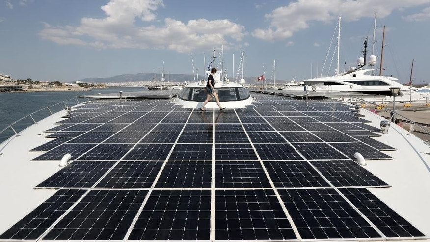 PlanetSolar press officer Julia Tames walks across the deck of the MS Turanor PlanetSolar, the world's largest solar-powered boat, moored at Zea Harbor, in Athens, on Tuesday Aug. 5, 2014. The 35-meter (115-foot) vessel is in Greece to take part in a Swiss-Greek underwater archaeology project to survey the seabed off a major prehistoric site, in hope of finding traces of what could be one of the earliest villages in Europe. (AP Photo/Thanassis Stavrakis)