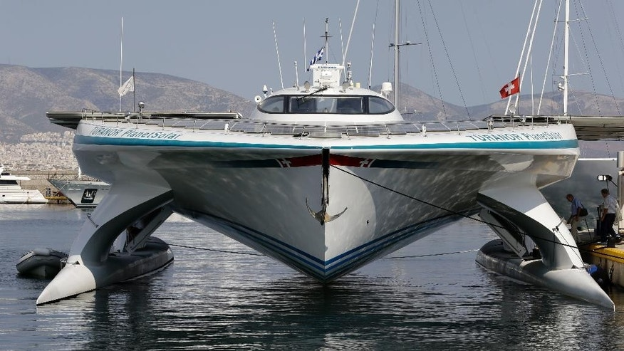 Visitors enter the MS Turanor PlanetSolar, the world's largest solar-powered boat, moored at Zea Harbor, in Athens, on Tuesday Aug. 5, 2014. The 35-meter (115-foot) vessel is in Greece to take part in a Swiss-Greek underwater archaeology project to survey the seabed off a major prehistoric site, in hope of finding traces of what could be one of the earliest villages in Europe. (AP Photo/Thanassis Stavrakis)