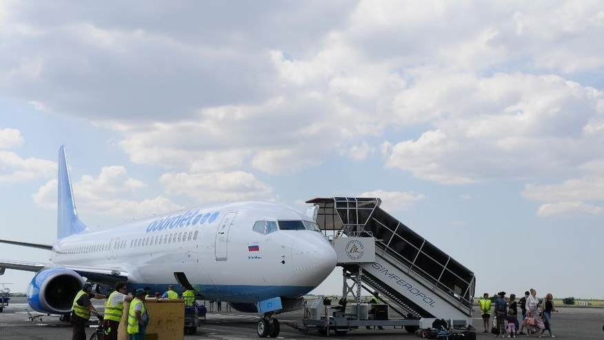 In this Tuesday, June 10, 2014 photo ground staff load up luggage on board Boeing of Russian low-cost airline Dobrolet  in Simferopol airport, Crimea. In July and August, tens of thousands of Russians sunning themselves on the beaches of Italy or the resorts of Turkey received an unpleasant surprise: the tour companies that had organized their trips had gone bust, stranding them in paradise and forcing them to pay their own way home. Sanctions imposed last week by the U.S. and European Union on key Russian industries could take months to bite, and so far the difficulties posed to Russia have been irritating but minor, from the closure of a low-cost airline on Monday Aug. 4, 2014 to Crimea,  to an oligarch's jet being stranded on the tarmac. But the recent collapse of Russia's tourism industry shows that cracks are already showing in the country's economy, after months of tension with the West and instability in neighboring Ukraine have sent its currency tumbling and investors scrambling. (AP Photo/ Alexander Polegenko)