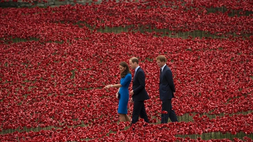 Britain's Prince William, the Duke of Cambridge, centre, walks with Kate, the Duchess of Cambridge, centre left and Prince Harry, as they view the Tower of London's 'Blood Swept Lands and Seas of Red' poppy installation, to commemorate the 100th anniversary of the outbreak of WWI, in London, Tuesday Aug. 5, 2014. Their visit to the work in progress installation, which currently consists of approximately 120,000 ceramic poppies and will finish with 888,246 poppies, was held Tuesday to mark the centenary of World War I. The final ceramic poppy will be placed on Armistice Day on November 11, with each poppy representing a British and Commonwealth military fatality from World War I.  (AP Photo/Matt Dunham)