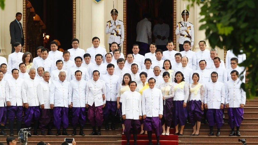 Cambodia's main opposition leader Sam Rainsy, foreground right, and his Deputy President Kem Sokha, foreground left, pose for photographs with their party lawmakers inside Royal Palace, in Phnom Penh, Cambodia, Tuesday, Aug. 5, 2014. Cambodia's opposition lawmakers-elect took sworn in Tuesday, to get their official parliamentary immunity by ending their 10-months boycott of parliament. (AP Photo/Heng Sinith)