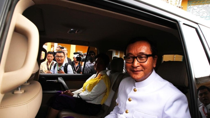 Cambodia's main opposition leader Sam Rainsy sits in a car after the swearing ceremony with his party lawmakers inside Royal Palace, in Phnom Penh, Cambodia, Tuesday, Aug. 5, 2014. Cambodia's opposition lawmakers-elect took sworn in Tuesday, to get their official parliamentary immunity by ending their 10-months boycott of parliament. (AP Photo/Heng Sinith)
