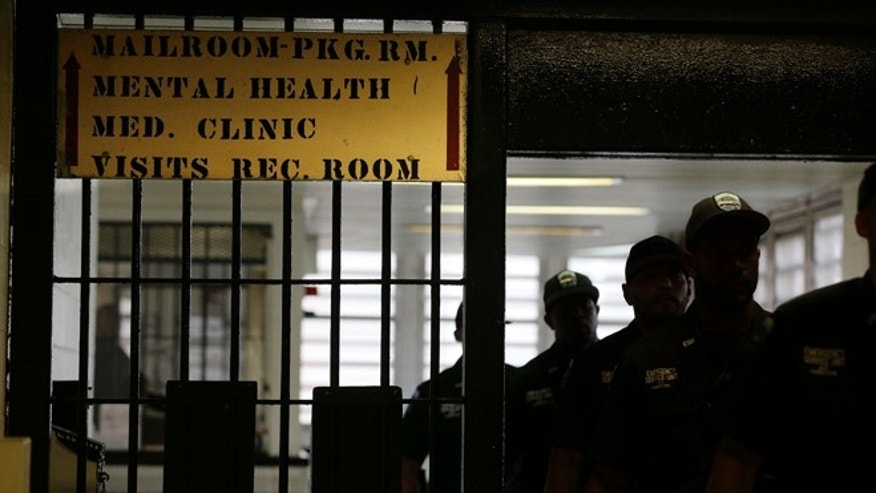 FILE - In this July 31, 2014 file photo, Rikers Island emergency services personnel walk through one of many gates inside the jail's juvenile detention facility in New York. The cityâs juvenile jails are extremely violent and unsafe, the result of a deeply ingrained culture of violence in which guards routinely violate constitutional rights of teenage inmates and subject them to ârampant use of unnecessary and excessive force,â federal prosecutors said in a scathing report released Monday, Aug. 4, 2014. (AP Photo/Julie Jacobson, File)