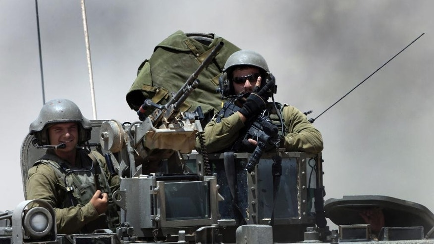 Israeli reserve soldiers are seen on the top of an armored personnel carrier returning to Israel from Gaza Strip, southern Israel, Monday, Aug. 4, 2014. A brief cease-fire declared by Israel and troop withdrawals slowed violence in the Gaza war Monday, but an attack on an Israeli bus that killed one person in Jerusalem underscored the tensions still simmering in the region as Israeli airstrikes resumed late in the day. (AP Photo/Tsafrir Abayov)