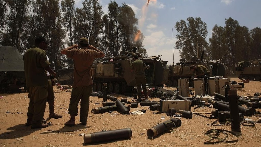 Israeli soldiers fire a mortar shell towards the Gaza Strip as the force are returning to Israel, near Israel Gaza border, Monday, Aug. 4, 2014. A brief cease-fire declared by Israel and troop withdrawals slowed violence in the Gaza war Monday, but an attack on an Israeli bus that killed one person in Jerusalem underscored the tensions still simmering in the region as Israeli airstrikes resumed late in the day. (AP Photo/Tsafrir Abayov)