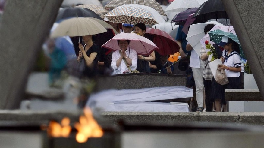 People pray for the atomic bomb victims in a rain at the Hiroshima Peace Memorial Park in Hiroshima, western Japan, early Wednesday, Aug. 6, 2014. Japan marked the 69th anniversary Wednesday of the atomic bombing of Hiroshima. (AP Photo/Kyodo News) JAPAN OUT, MANDATORY CREDIT