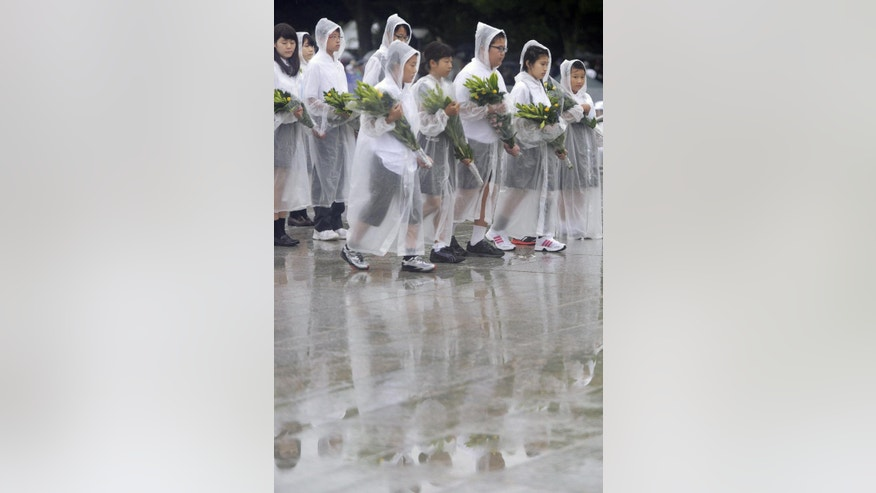 Children prepare to offer flowers to the atomic bomb victims during a ceremony at the Hiroshima Peace Memorial Park in Hiroshima, western Japan, Wednesday, Aug. 6, 2014. Japan marked the 69th anniversary Wednesday of the atomic bombing of Hiroshima. (AP Photo/Kyodo News) JAPAN OUT, MANDATORY CREDIT