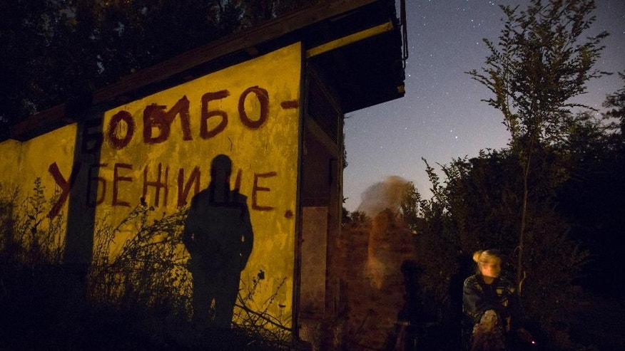 Local residents sit near an entrance to a bomb shelter as they exit to get some fresh air during a short cease fire in Petrovsky district in the city of Donetsk, eastern Ukraine Tuesday, Aug. 5, 2014. (AP Photo/Dmitry Lovetsky)