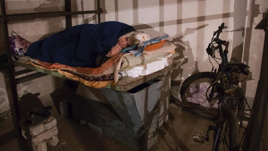 A woman sleeps in a bomb shelter as she hides from night shelling, in Petrovsky district in the city of Donetsk, eastern Ukraine Monday, Aug. 4, 2014. (AP Photo/Dmitry Lovetsky)