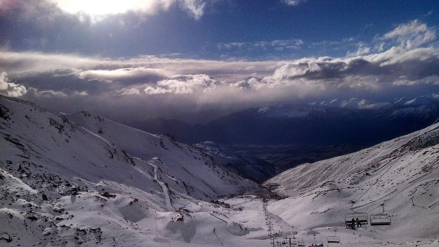 In this Thursday, July 31, 2014 photo, skiers and snowboarders enjoy clear skies at The Remarkables ski area near Queenstown, New Zealand. The Remarkables is one of several large ski areas that has been making snow at record rates following the warmest start to winter ever recorded. Scientists said New Zealand's glaciers and ice are melting at alarming rates due to climate change. (AP Photo/Richard Savoie)