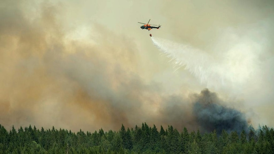 A helicopter dumps its load of water on the wildfire just outside the evacuated village of Gammelby near Sala, Central Sweden, Monday, Aug. 4, 2014. The fire, covering thousands of hectares, is in its fifth day and firefighters believe it will burn for weeks or even months. It is classified as the worst forest fire in Sweden's modern history. (AP Photo/Fredrik Sandberg, TT News Agency)       SWEDEN OUT