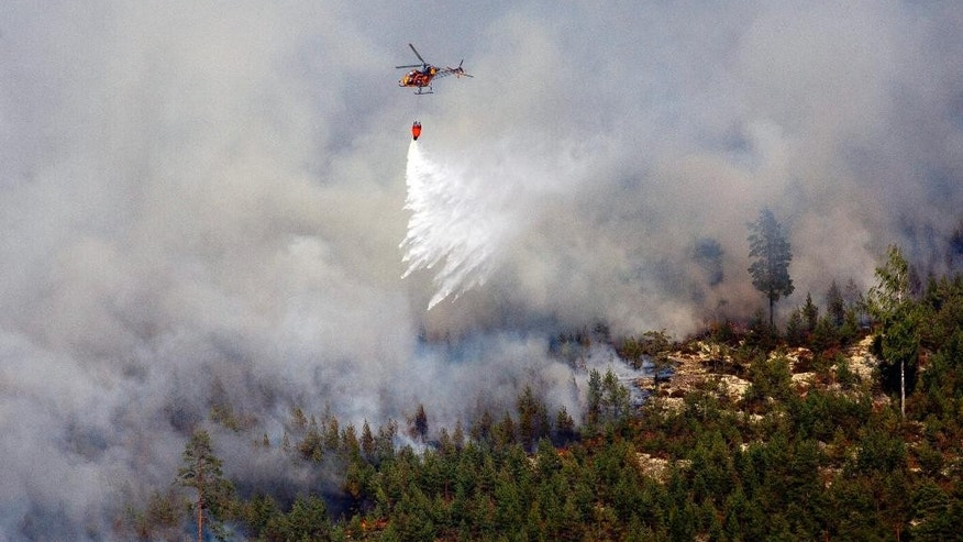 A fire fighting helicopter dumps its load on the wildfire front at the village of Rorbo near Sala, Central Sweden, on Sunday Aug. 3, 2014. The fire has swept over a wide swathe of land for nearly a week, and firefighters predict it will burn for weeks to come. It is classified as the worst forest fire in Sweden's modern history. (AP Photo / Jocke Berglund, file)  SWEDEN OUT