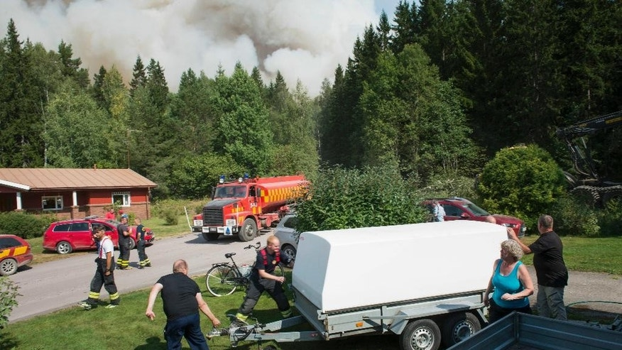 Home owners and emergency personnel prepare to evacuate a village threatened by the approaching forest fire near Sala, Central Sweden, on Monday Aug. 4, 2014. The fire has swept over a wide swathe of land for nearly a week, and firefighters predict it will burn for weeks to come. It is classified as the worst forest fire in Sweden's modern history.  (AP Photo / Fredrik Sandberg)  SWEDEN OUT