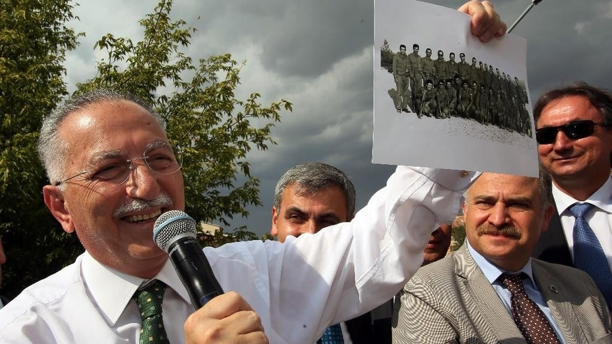 "Presidential candidate for upcoming Aug. 10, 2014 election Professor Ekmeleddin Ihsanoglu, the former head of the Organization of Islamic Cooperation, smiles as he shows a photo showing him with friends during his military service in Izmir, in Ankara, Turkey, Monday, Aug. 4, 2014. Ihsanoglu, who is supported by nearly all opposition parties, has highlighted credentials as a champion of the Palestinians' cause, national unity as ""a president for all Turkish citizens"" and stability during his campaign for the presidential elections pitting him against Prime Minister Recep Tayyip Erdogan.(AP Photo/Volkan Yildirim)"
