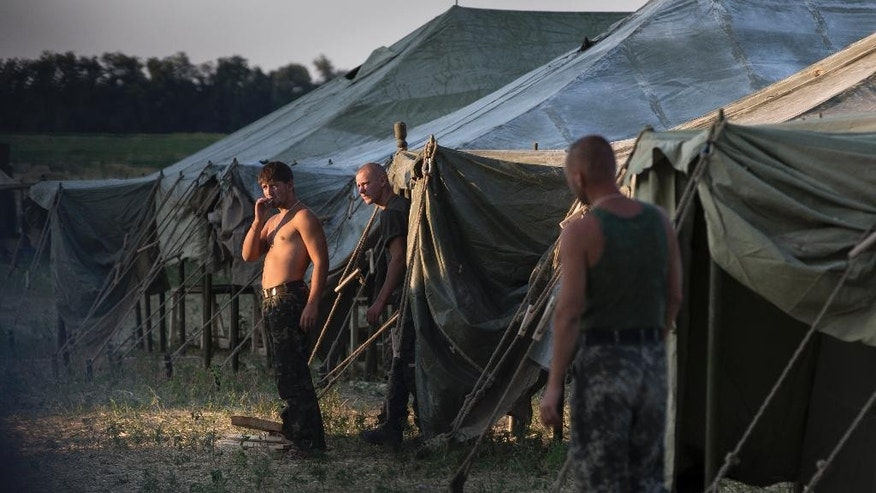 Ukrainian soldiers, who fled the conflict territory, spend their time at a tent camp as the sun sets over the scene near the Russia-Ukraine border just outside the village of Gukovo, Rostov-on-Don region, Southern Russia, Monday, Aug. 4, 2014. A Russian border security official said Monday that more than 400 Ukrainian soldiers have crossed into Russia. The Russian official said the soldiers deserted the Kiev government and the Russian side opened a safe corridor. (AP Photo/Alexander Zemlianichenko)