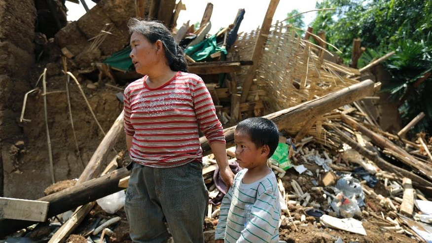 A woman stands next to an injured child near a damaged house following Sunday's earthquake in the town of Longtoushan in Ludian County in southwest China's Yunnan Province Tuesday, Aug. 5, 2014. Rescuers raced Tuesday to evacuate villages near rising lakes formed by landslides, complicating relief efforts following the strong earthquake in southern China that killed over 300 people and has left thousands homeless. (AP Photo/Andy Wong)