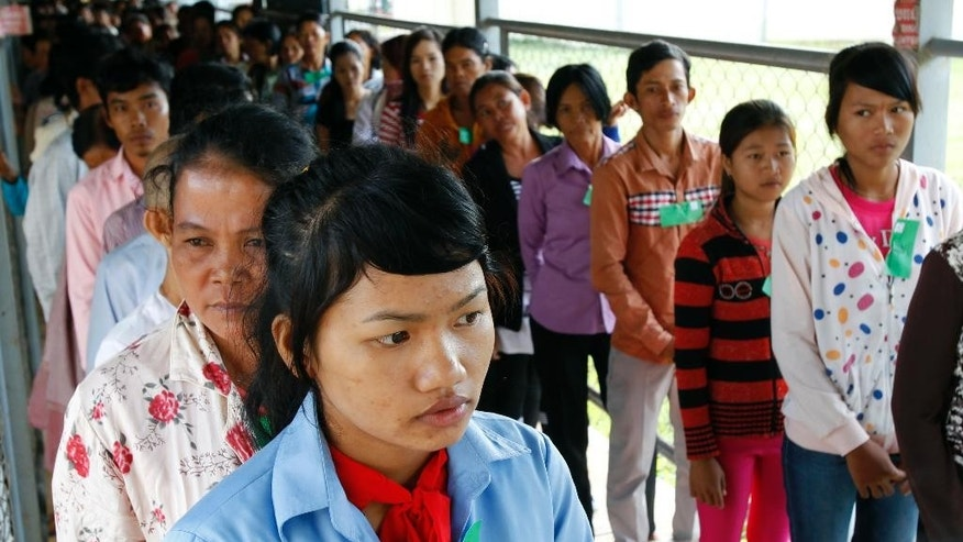 In this July 30, 2014 photo, Cambodians line up at a court entrance before a hearing to prepare for the genocide trial of two surviving leaders Khieu Samphan and Noun Chea, at the U.N.-backed war crimes tribunal in Phnom Penh, Cambodia. A U.N.-assisted court on Thursday, Aug. 7, 2014 will deliver its verdicts in a case against the two most senior surviving leaders of Cambodia's Khmer Rouge, charged with crimes against humanity. (AP Photo/Heng Sinith)