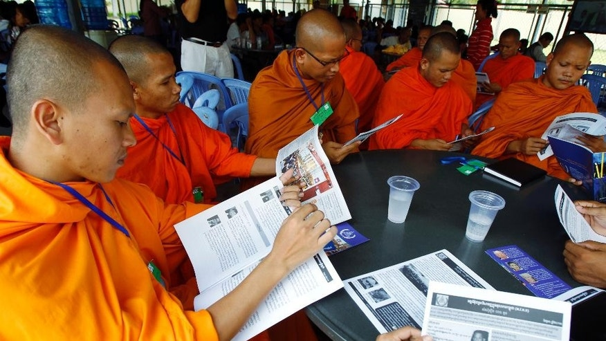 In this July 30, 2014 photo, Cambodian Buddhist monks read the court document books during a court break of a hearing to prepare for the genocide trial of two surviving leaders Khieu Samphan and Noun Chea, at the U.N.-backed war crimes tribunal in Phnom Penh, Cambodia. A U.N.-assisted court on Thursday, Aug 7, 2014 will deliver its verdicts in a case against the two most senior surviving leaders of Cambodia's Khmer Rouge, charged with crimes against humanity. (AP Photo/Heng Sinith)