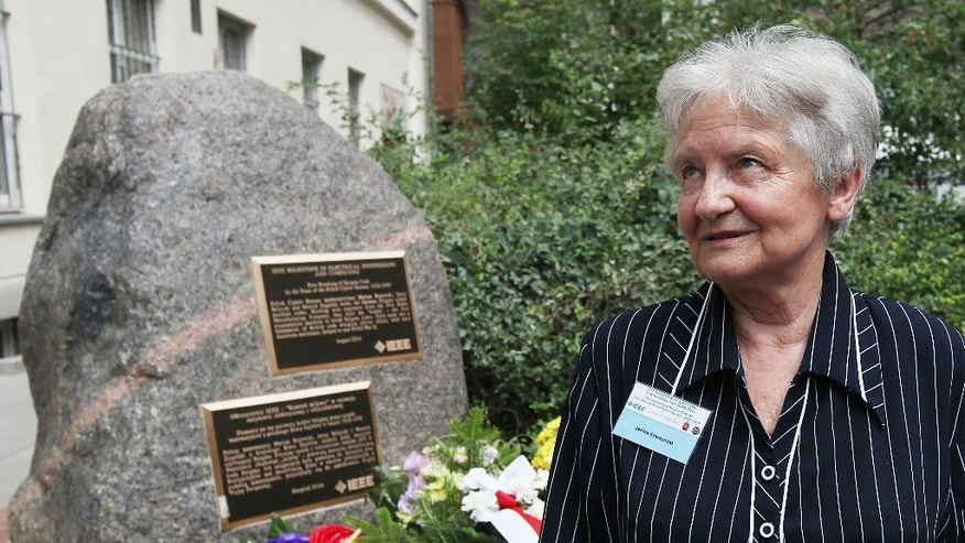"Janina Sylwestrzak, the daughter of Marian Rejewski, one of three Polish mathematicians who in 1932 broke the German Enigma cipher machine is talking to reporters in fron of a memorial plaque unveiled to the three scientists in Warsaw, Poland, Tuesday, Aug. 5, 2014. The late Rejewski, Jerzy Rozycki and Henryk Zygalski were honored on Tuesday with the ""Milestone"" distinction by the global Institute of Electrical and Electronics Engineers for helping the Allied victory and thus saving lives. (AP Photo/Czarek Sokolowski)"