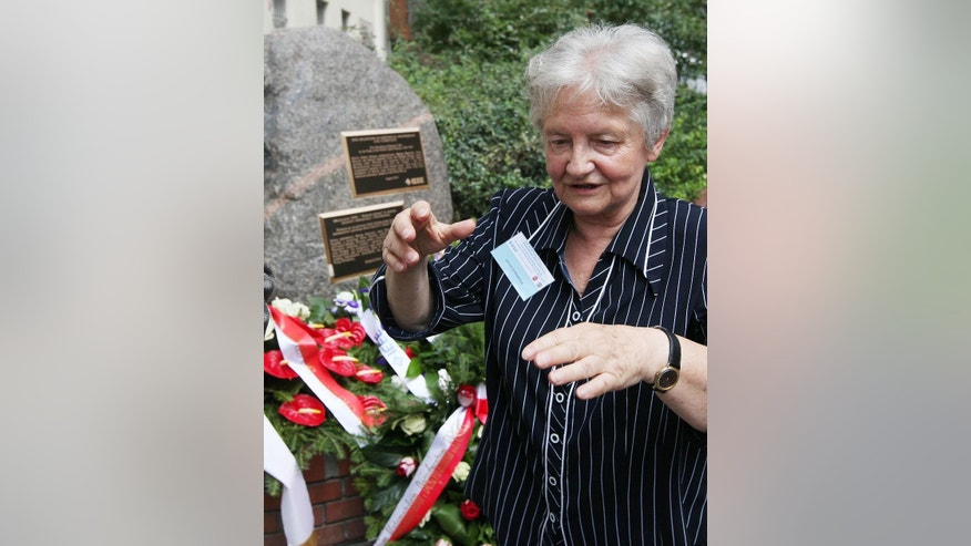 "Janina Sylwestrzak, the daughter of Marian Rejewski, one of three Polish mathematicians who in 1932 broke the German Enigma cipher machine is talking to reporters in front of a memorial plaque unveiled to the three scientists in Warsaw, Poland, Tuesday, Aug. 5, 2014. The late Rejewski, Jerzy Rozycki and Henryk Zygalski were honored on Tuesday with the ""Milestone"" distinction by the global Institute of Electrical and Electronics Engineers for helping the Allied victory and thus saving lives. (AP Photo/Czarek Sokolowski)"