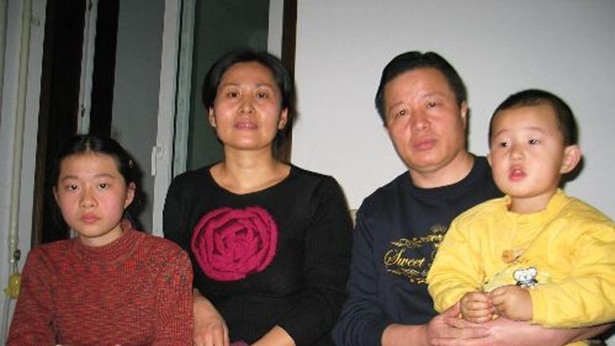In this photo taken Jan. 6, 2006 and released by Hu Jia, Gao Zhisheng, a human rights lawyer, second right, poses for photos with his son Gao Tianyu, right, and his wife Geng He, second left, and daughter Geng Ge, left, at their home in Beijing, China. A fiery critic of China's authoritarian government whose imprisonment and accounts of torture triggered international criticism of Beijing appears set for release Thursday, Aug. 7, 2014 amid mounting concerns the authorities will continue to deny the lawyer freedom outside prison. (AP Photo/Hu Jia)