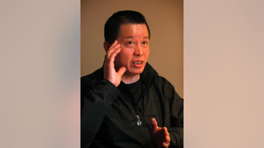 FILE - In this April 7, 2010 file photo, Gao Zhisheng, a human rights lawyer, gestures during an interview at a tea house in Beijing, China. A fiery critic of China's authoritarian government whose imprisonment and accounts of torture triggered international criticism of Beijing appears set for release Thursday, Aug 7, 2014 amid mounting concerns the authorities will continue to deny the lawyer freedom outside prison. (AP Photo/Gemunu Amarasinghe, File)